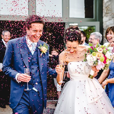 Happy couple showered in confetti as they leave the Tythe Barn