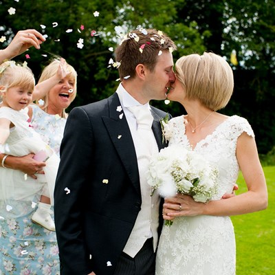 Wedding couple kiss in garden with happy child and mother looking on