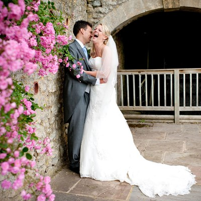 Newly weds share a joke beside the waterwheel and pink garden roses