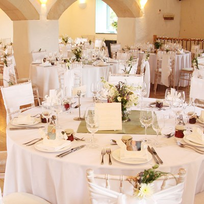 Reception laid in the Watermill with white sashes on the chiavari chairs