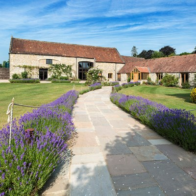 Beatuful shot of Tythe Barn with lavender lined path and blues skies