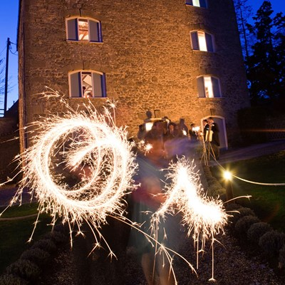 Sparkler circles with background of Watermill at night