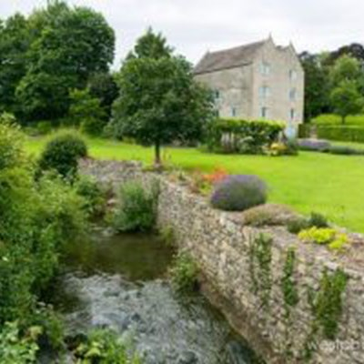 Watermill garden with stream in foreground in the Summer