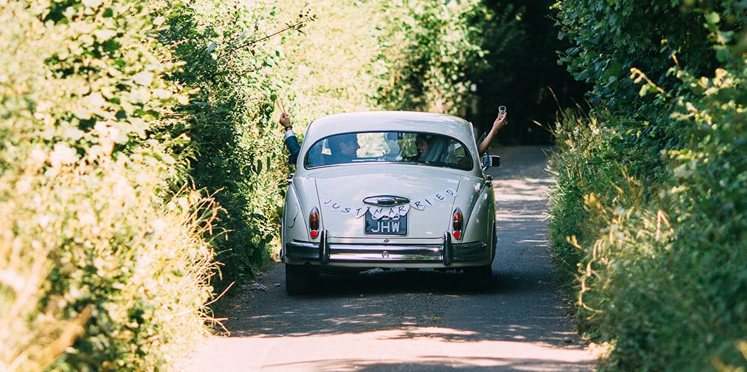 Jaguar disappearing down country lane with couple and Just Married sign