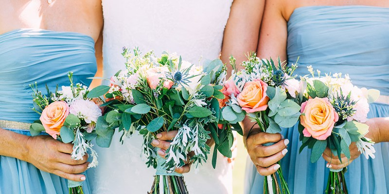 four beautiful bouquets held by bridesmaids in blue