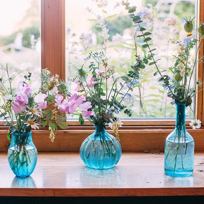 three blue glass vases with arrangements