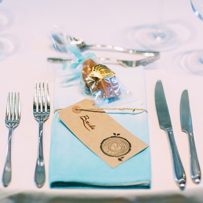 Place setting with blue napkin and favour