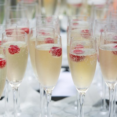 Glasses of sparkling wine served with raspberries