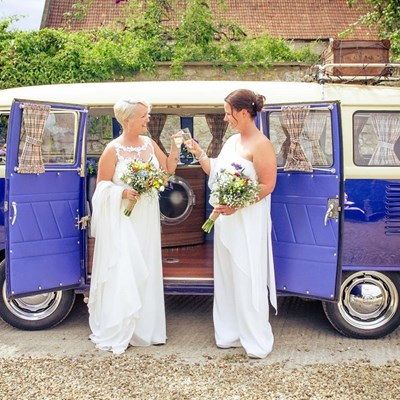 Two Brides toast each other beside their deep blue campervan