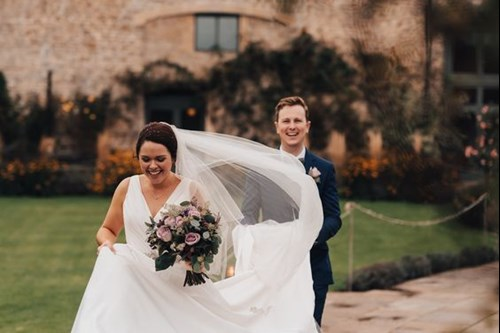 Bride and Groom walk down pathway at Barn wedding venue on a windy Autumn day