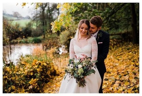 Bride and Groom by lake at Priston Mill with autumn leaves on the ground