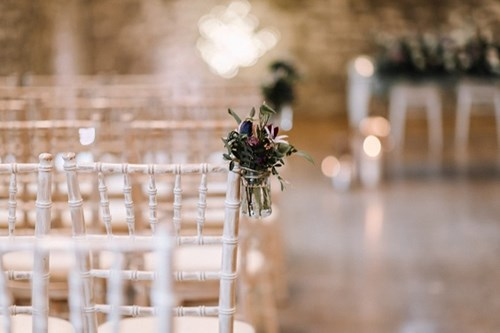 Wedding ceremony set with candles and pretty jars of flowers attached to the chairs.