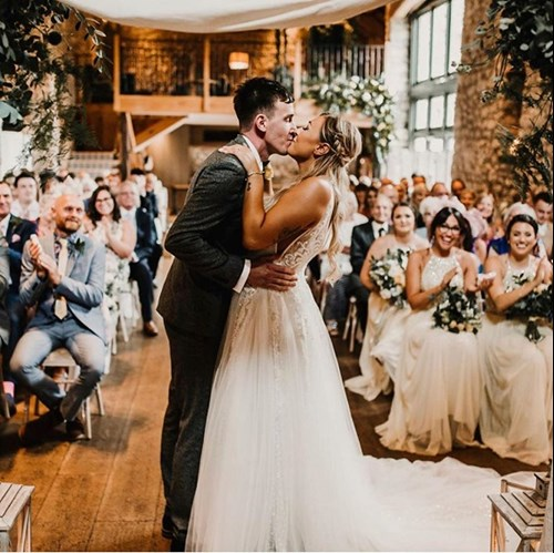 Bride and Groom just married at Barn wedding venue in Autumn with guests clapping