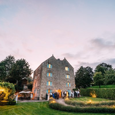Watermill wedding venue near Bath during the evening with guests enjoying drinks outside