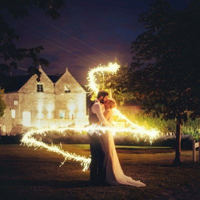 Bride and groom kissing in the light of a sparkler pattern surrounding them