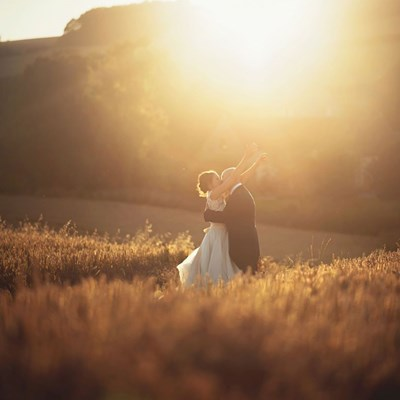 Bride and groom pose in field at sunset at Priston Mill