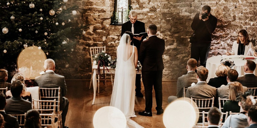 Couple getting married at Christmas time in the Tythe Barn wedding venue