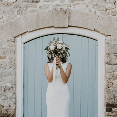 Bride poses with her bouquet covering her face