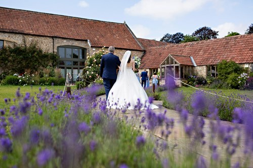 Bride walking to the Tythe Barn at Prison Mill