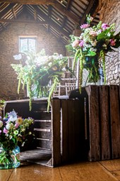 Flowers on crates at Barn wedding venue Priston Mill